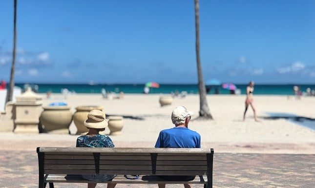 Old couple sitting by the beach enjoying the sun