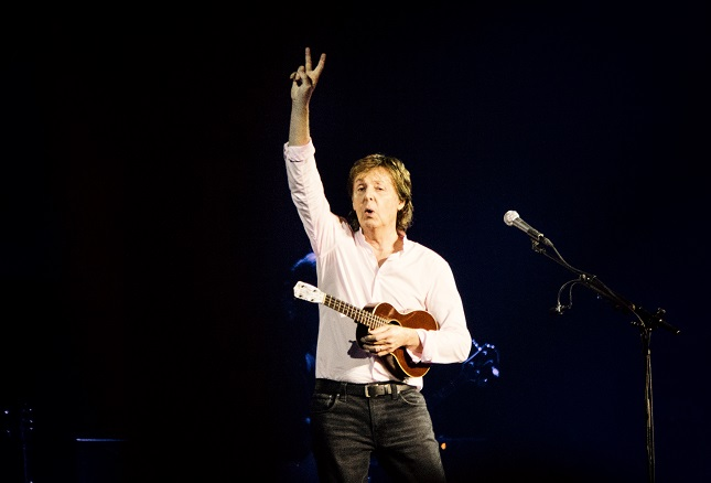 Paul McCartney playing guitar on a live concert